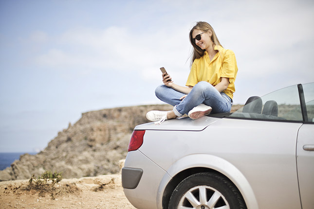 Girl sitting on car looking for car insurance
